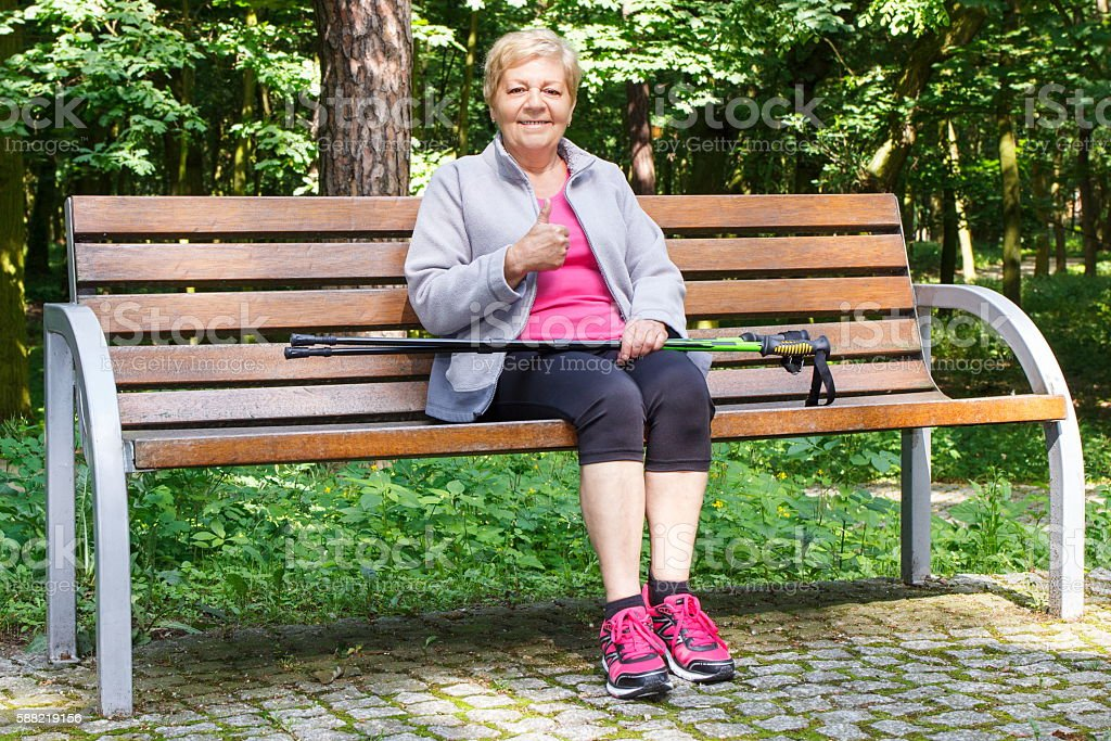 Senior woman resting after nordic walking and showing thumbs up stock photo