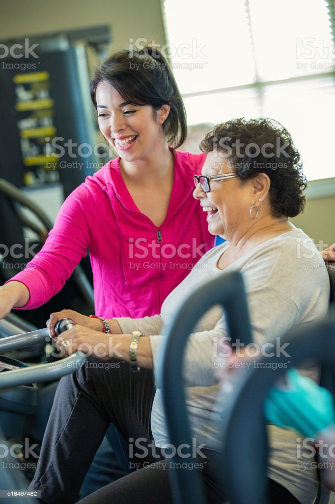Senior woman rides stationary bicycle stock photo