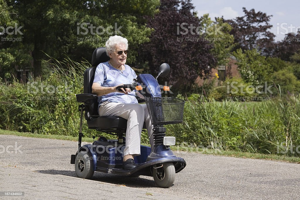 senior woman riding an electric scooter stock photo