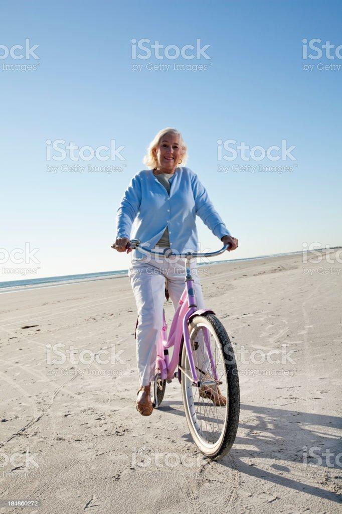 Senior woman riding bicycle on beach royalty-free stock photo