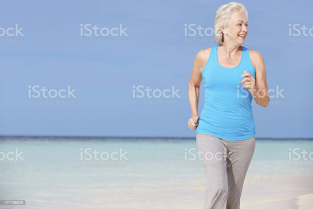 Senior Woman Running On Beautiful Beach royalty-free stock photo