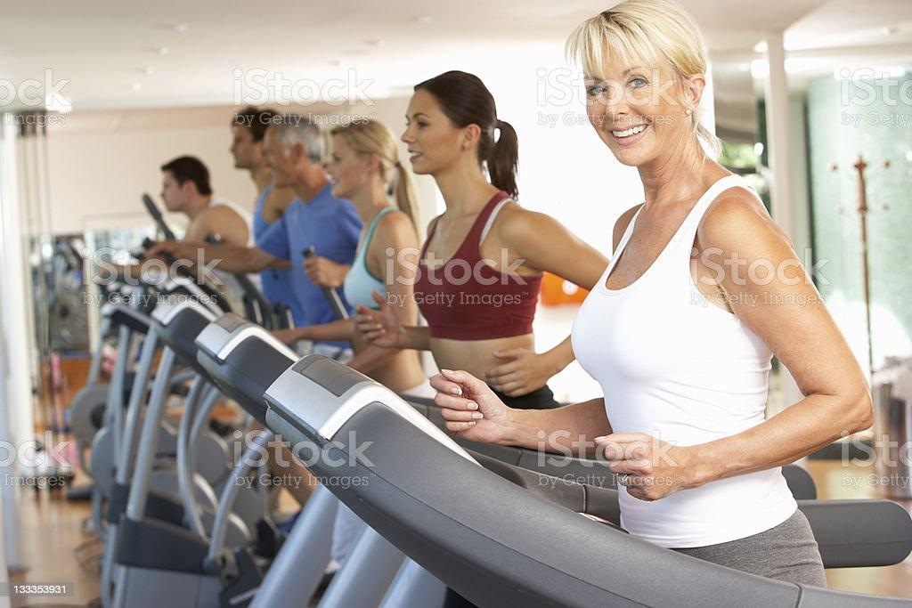 Senior woman running on treadmills in gym stock photo