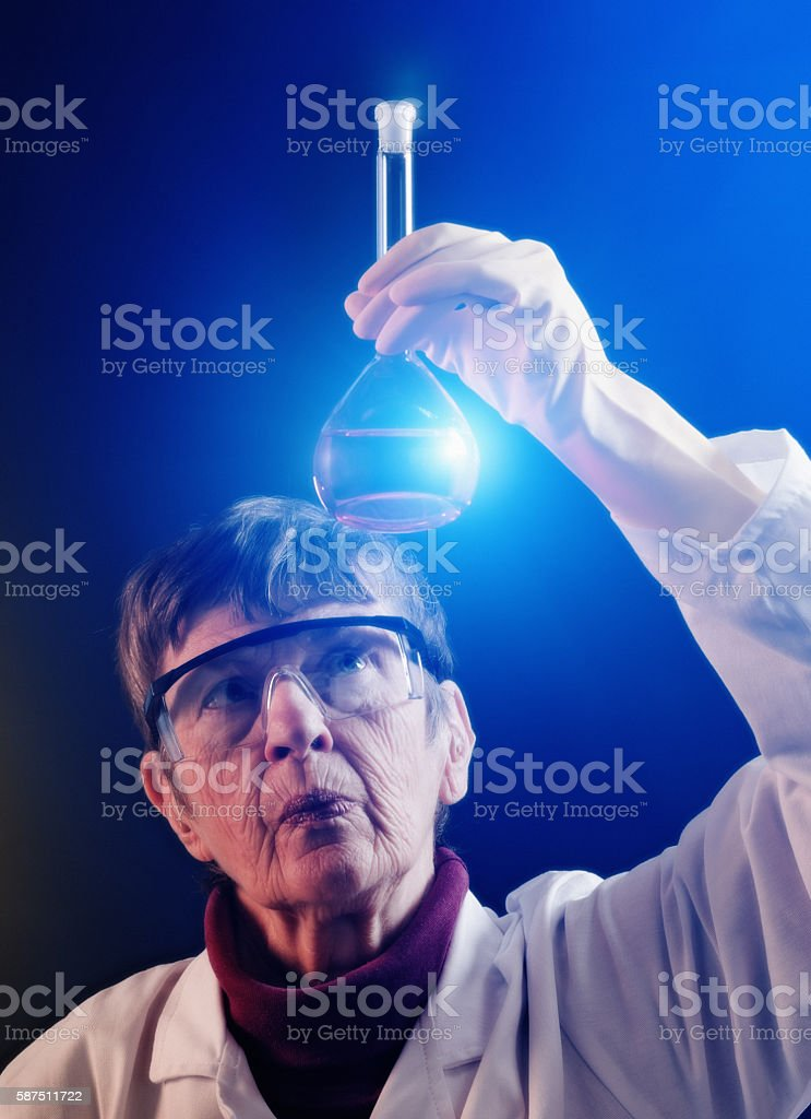 Senior woman scientist studies spotlit fluid in lab flask seriously stock photo