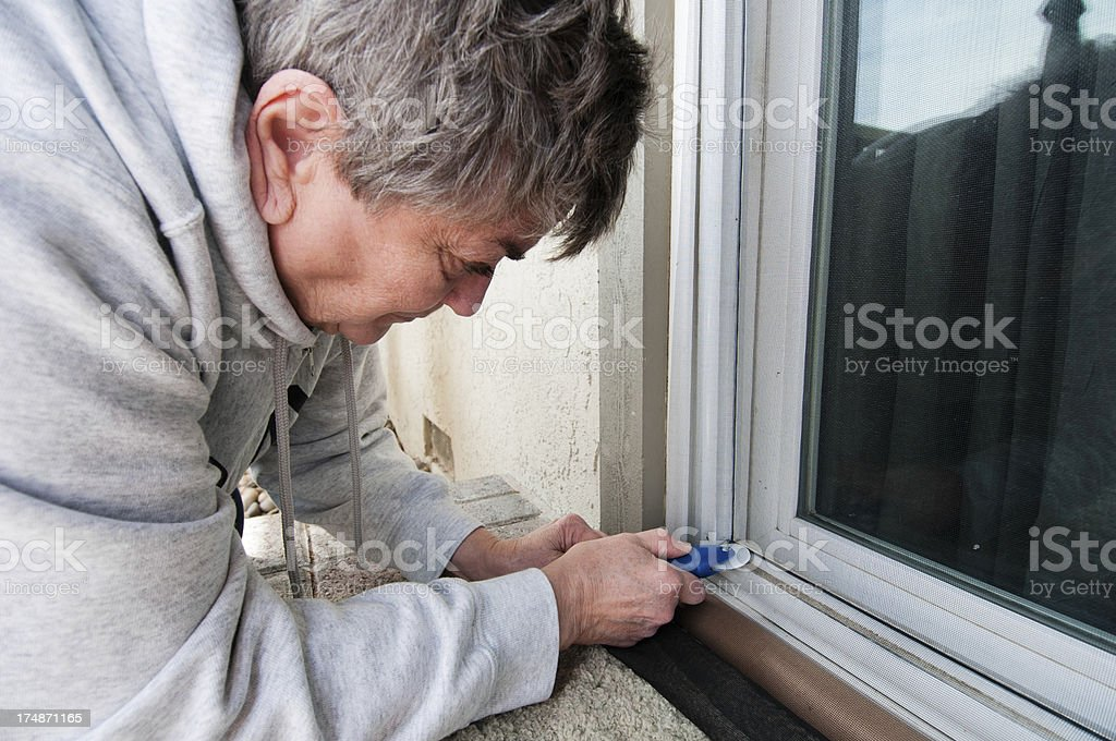Senior Woman Screen Door Repair stock photo