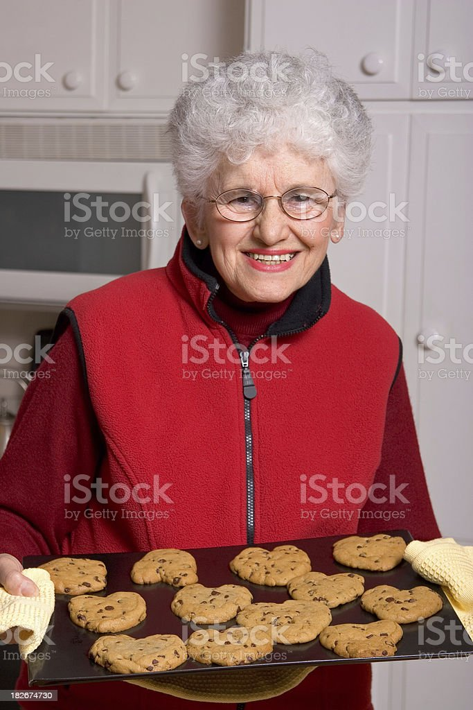 Senior Woman Serving Fresh Baked Cookies royalty-free stock photo