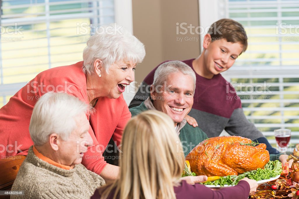 Senior woman serving roasted turkey to big family stock photo