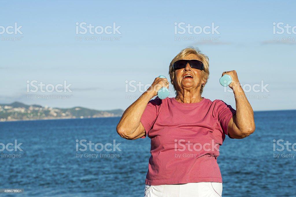 Femme âgée annonce sur la plage. photo libre de droits