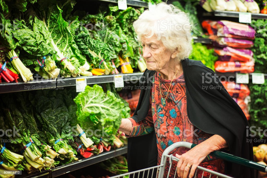 Senior Woman Shopping for Vegetables in Grocery Store stock photo