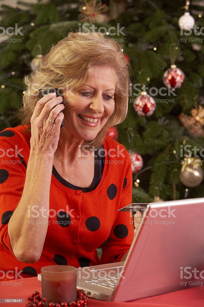 Senior Woman Shopping Online For Christmas Gifts On Phone royalty-free stock photo