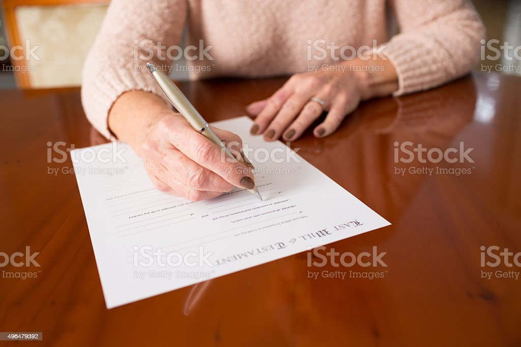 Senior Woman Signing Last Will And Testament At Home stock photo