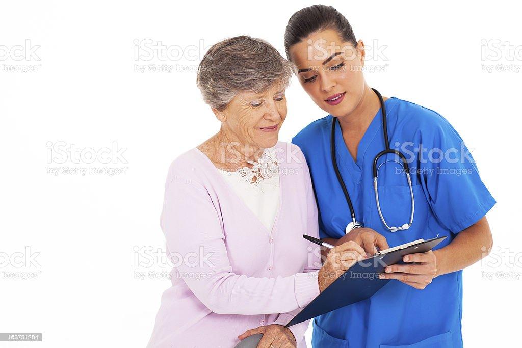 senior woman signing medical form royalty-free stock photo