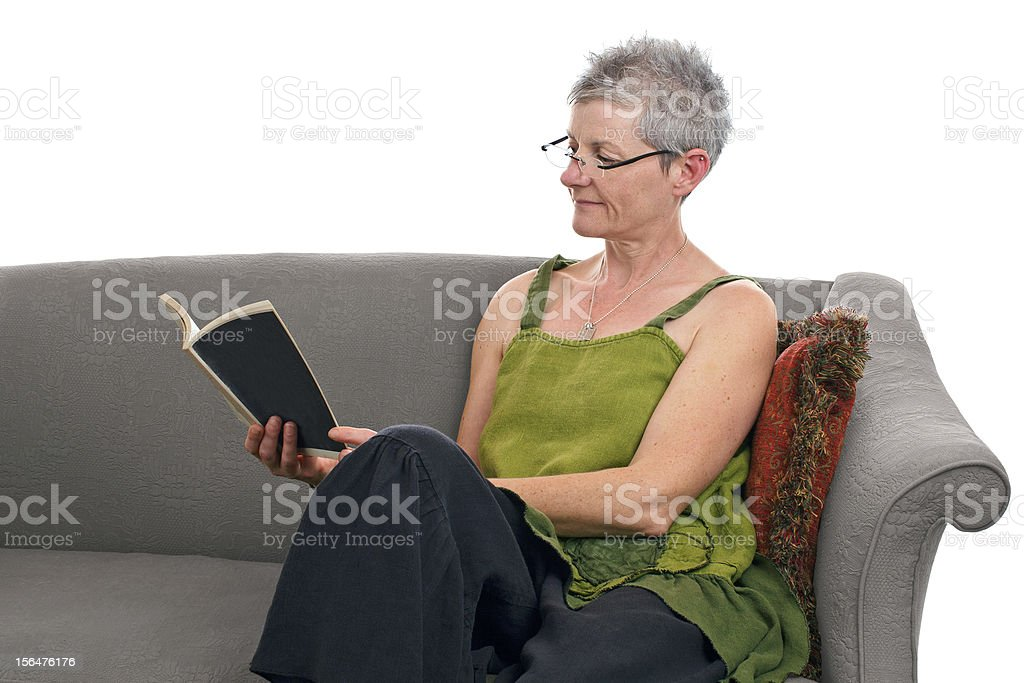 Senior woman sits and reads a book royalty-free stock photo
