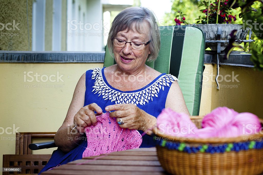 Senior woman sits on the balcony and knits a pullover royalty-free stock photo