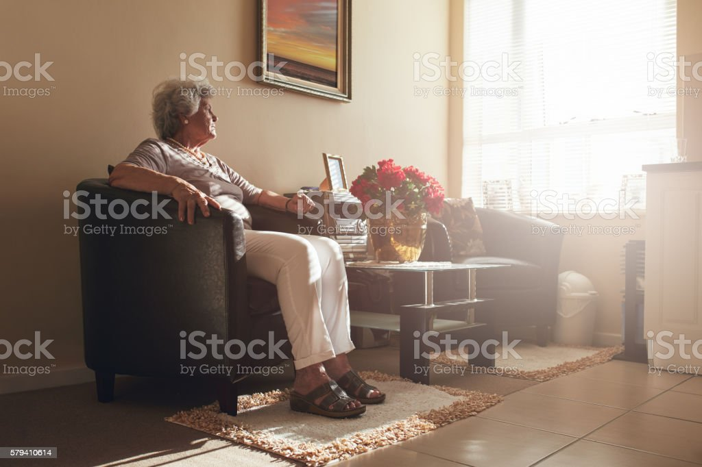 Senior woman sitting alone on a chair at home stock photo
