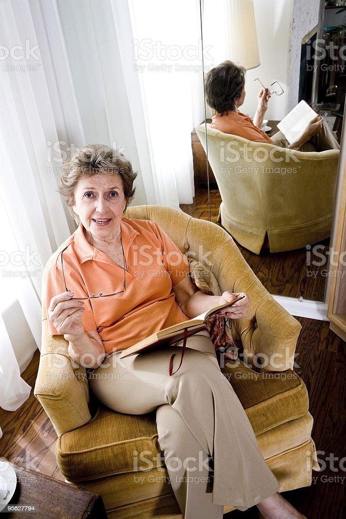 Senior mujer sentada en casa, leyendo un libro foto de stock libre de derechos