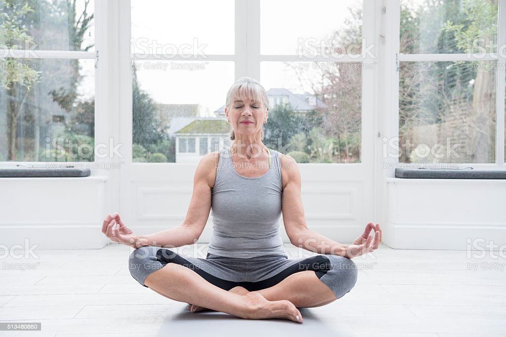 Senior woman sitting cross legged doing yoga at home stock photo