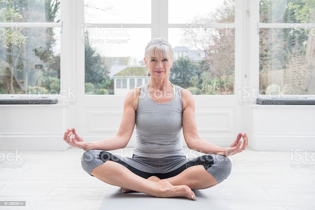 Senior woman sitting cross legged, meditating stock photo