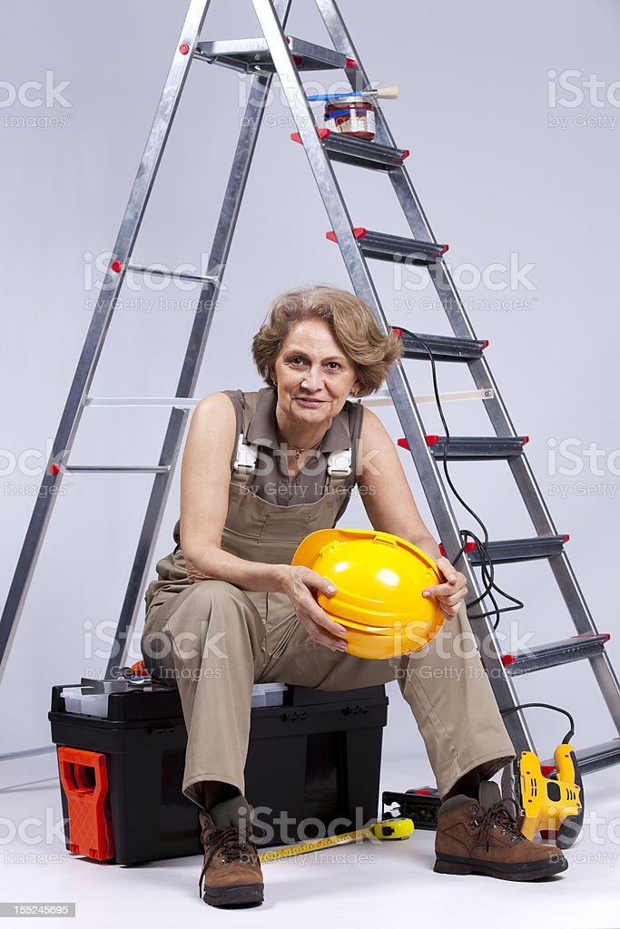 Senior woman sitting in a toolbox royalty-free stock photo