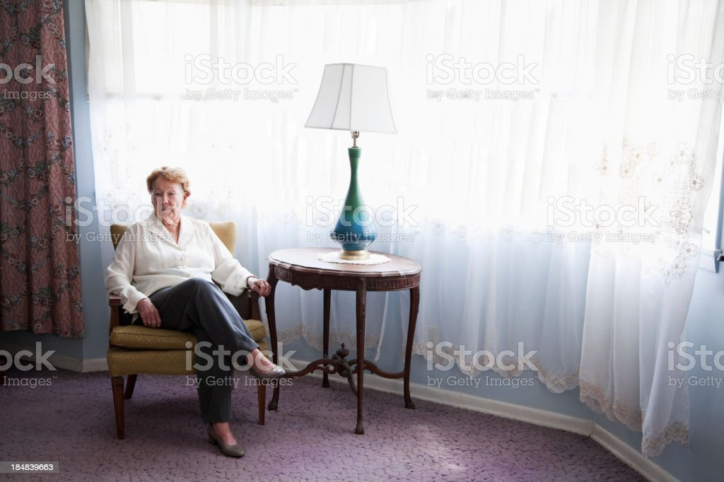Senior woman sitting in chair at home stock photo
