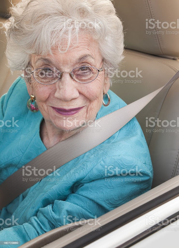 senior woman sitting in driver's seat stock photo