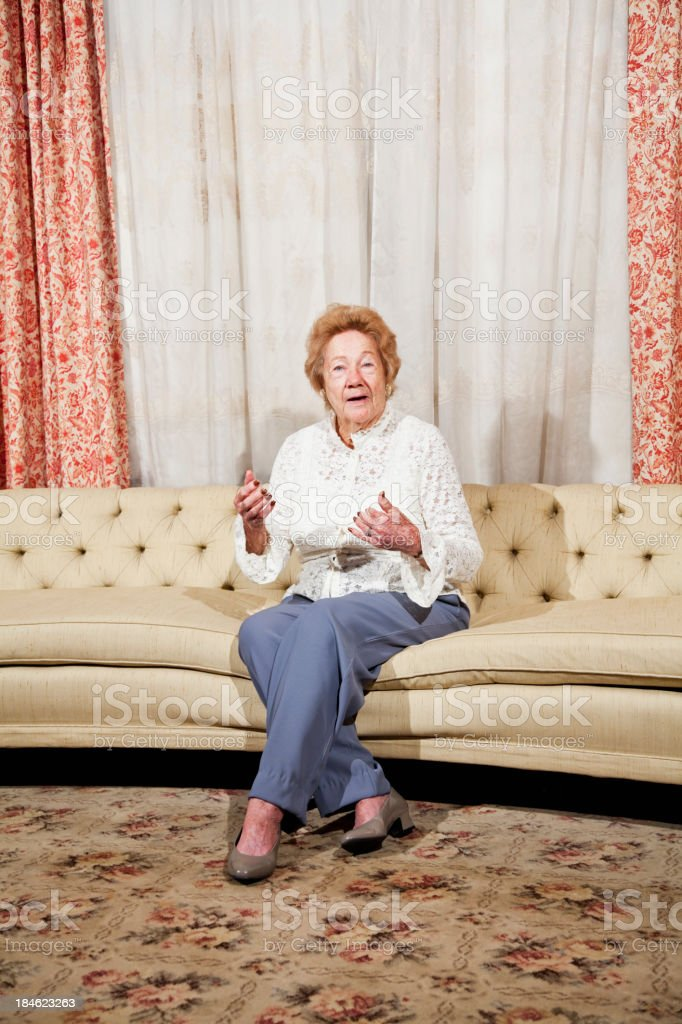 Senior woman sitting in formal living room stock photo