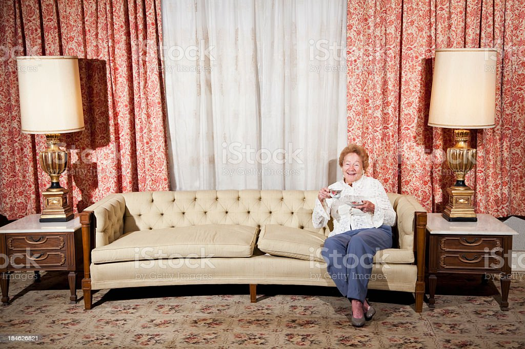 Senior woman sitting in living room drinking tea stock photo