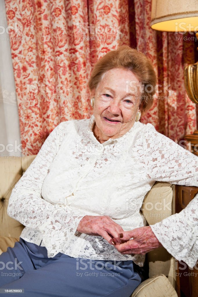 Senior woman sitting in living room stock photo