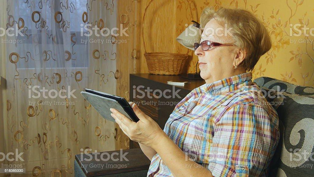 Senior mujer sentada en el sofá con tableta electrónica foto de stock libre de derechos