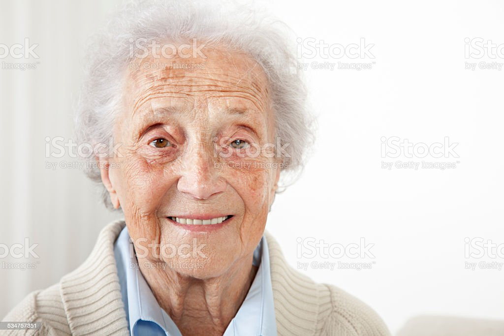 Senior woman sitting on a bench and looking into camera stock photo