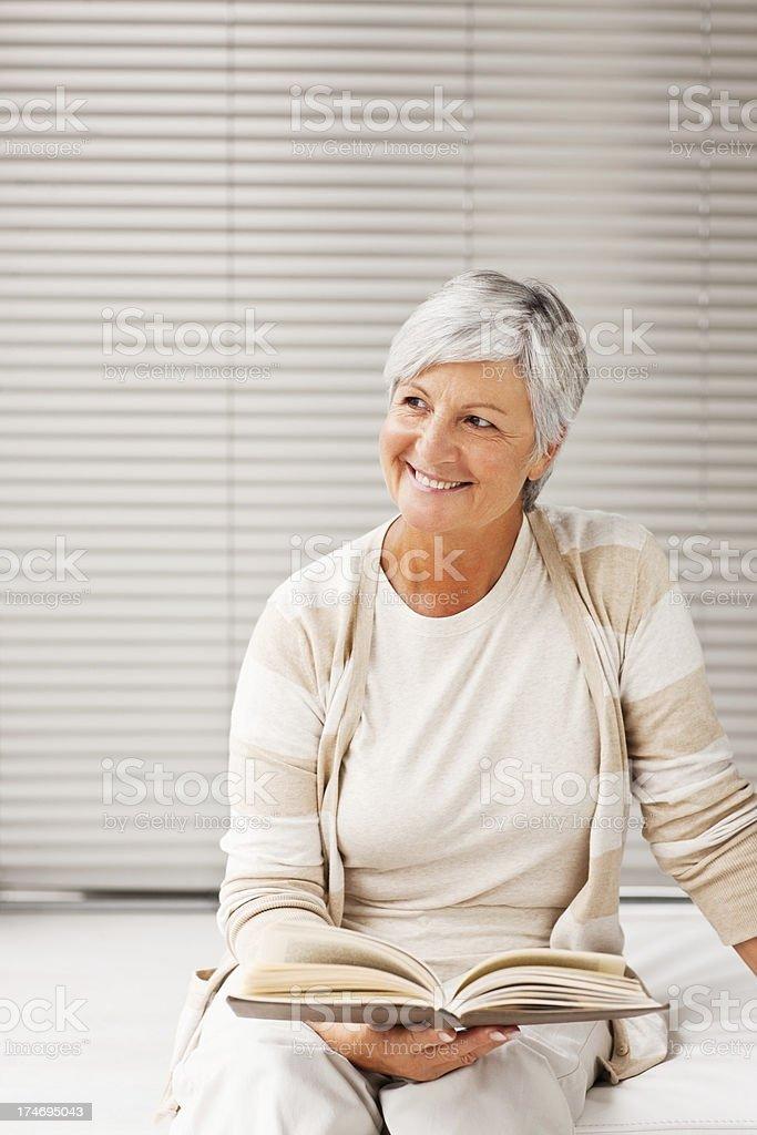 Senior woman sitting on a cane chair holding magzine royalty-free stock photo