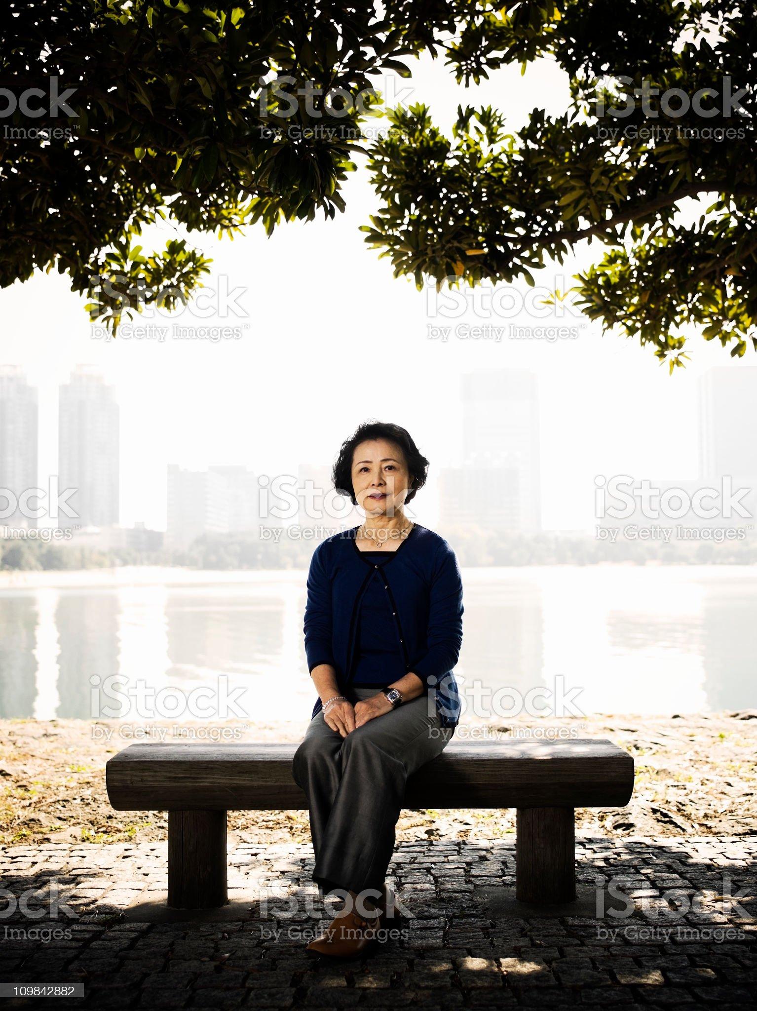 Senior Woman Sitting on a Park Bench royalty-free stock photo