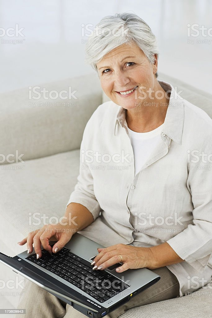 Senior woman sitting on couch and using laptop royalty-free stock photo