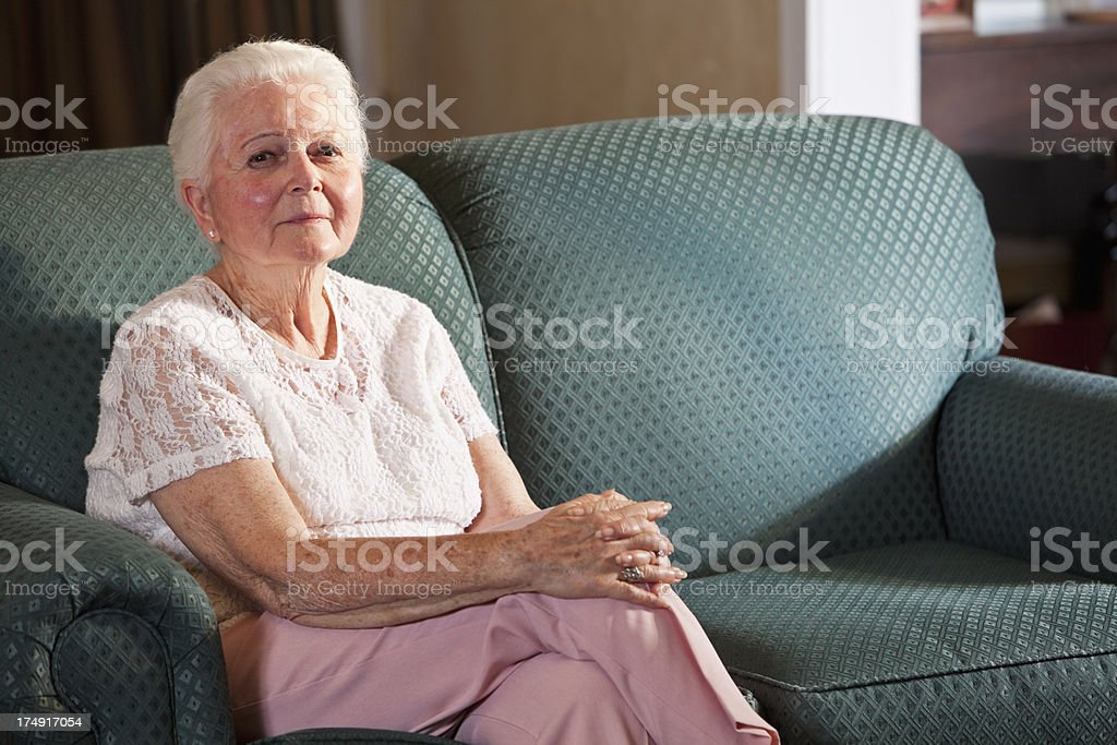 Senior woman sitting on couch royalty-free stock photo