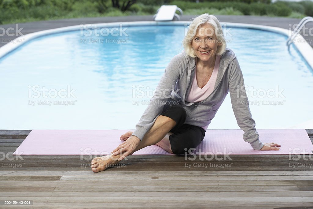 Senior woman sitting on mat smiling, portrait stock photo
