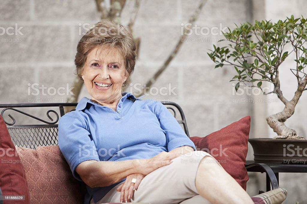Senior woman sitting on patio royalty-free stock photo