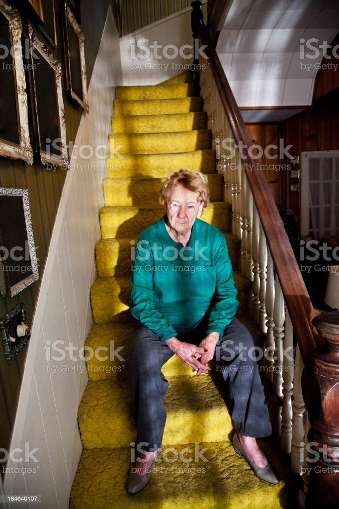 Senior woman sitting on staircase stock photo