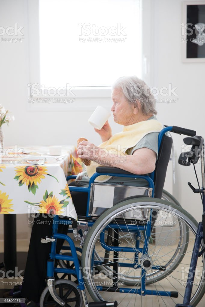 Senior Woman Sitting On The Wheelchair Waiting For Breakfast At The Care Center stock photo