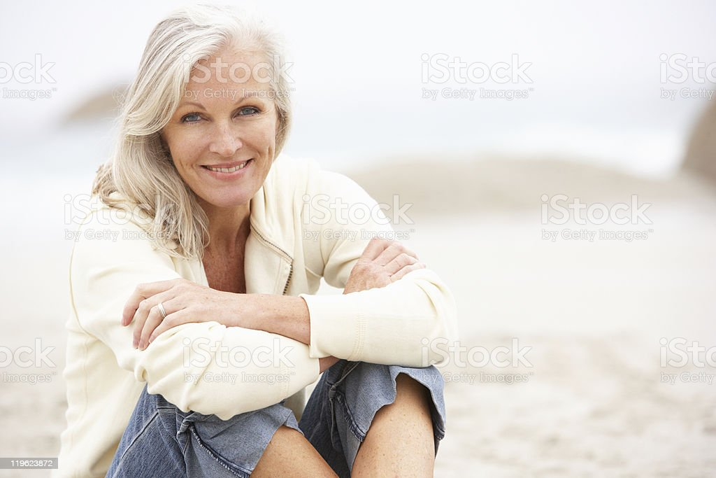 Senior Woman Sitting On Winter Beach stock photo