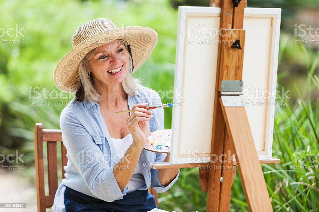 Senior woman sitting outdoors, painting stock photo
