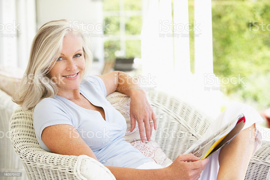 Senior Woman Sitting Outside Reading Magazine stock photo