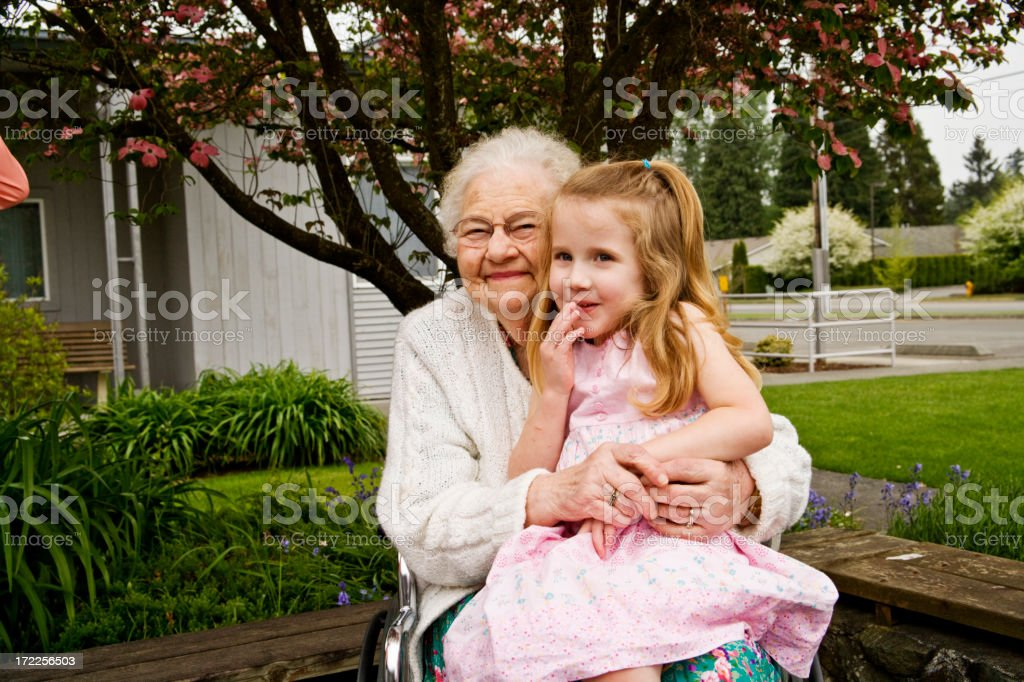 Senior woman sitting with young girl in her lap stock photo