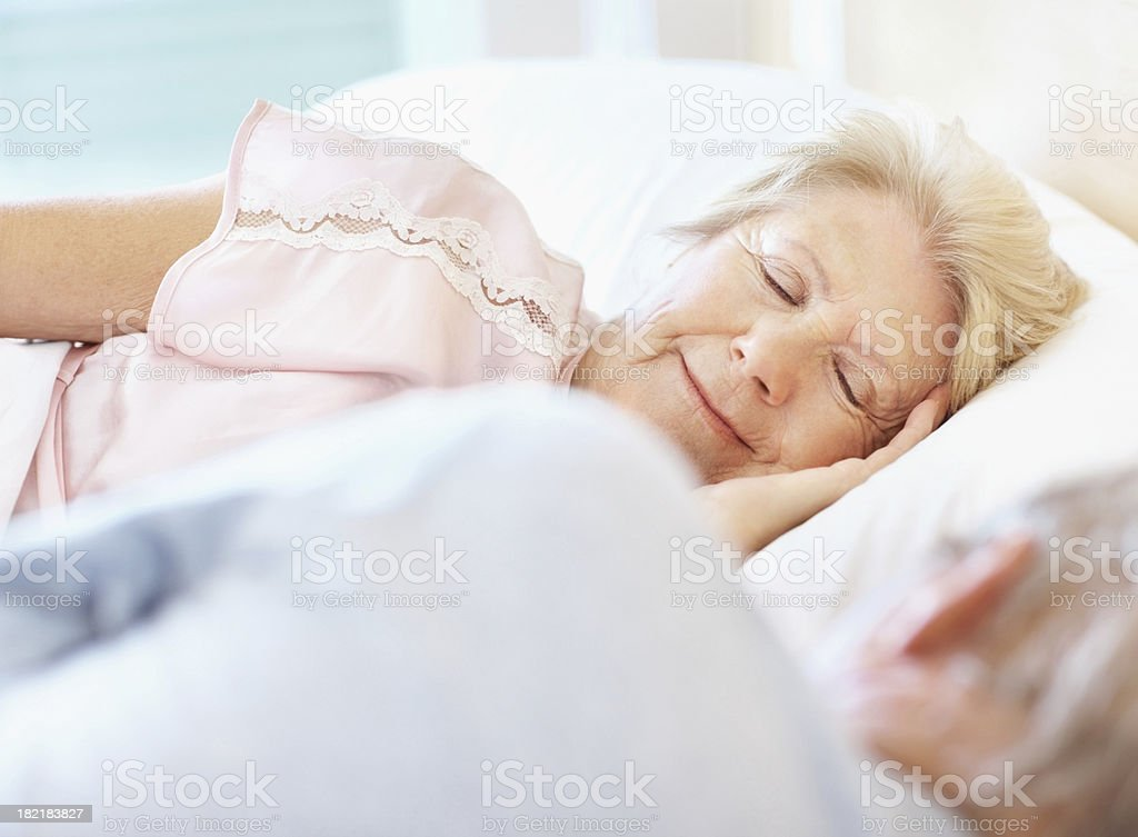 Senior woman sleeping besides her husband royalty-free stock photo