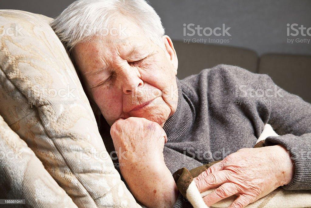 senior woman sleeping in armchair stock photo