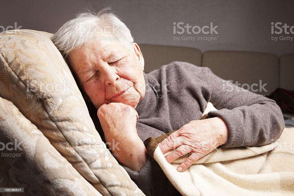senior woman sleeping in chair stock photo