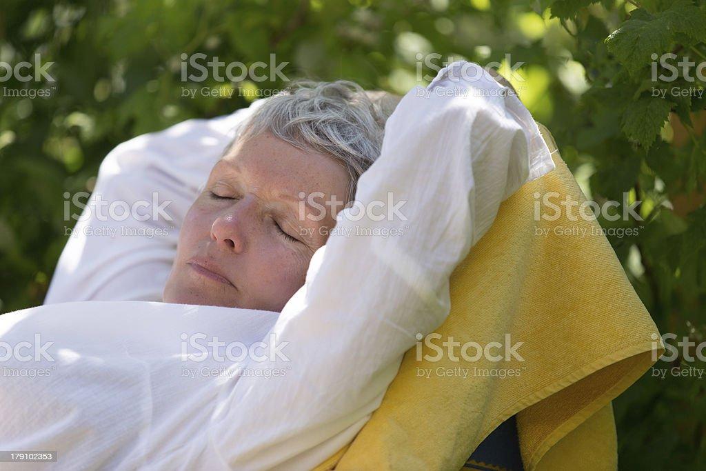 Senior woman sleeping on lounger royalty-free stock photo