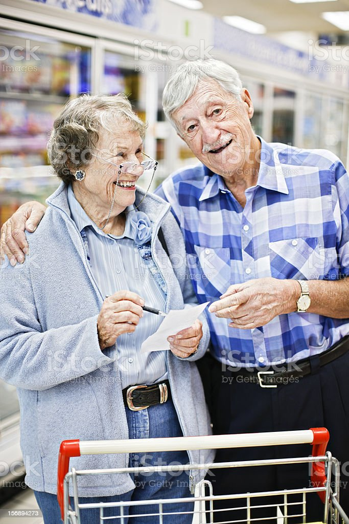 Senior woman smiles as happy husband hugs her in supermarket stock photo