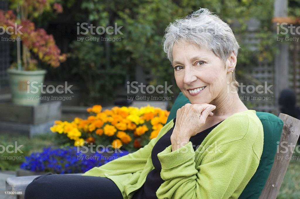 A senior woman smiling and sitting outside royalty-free stock photo