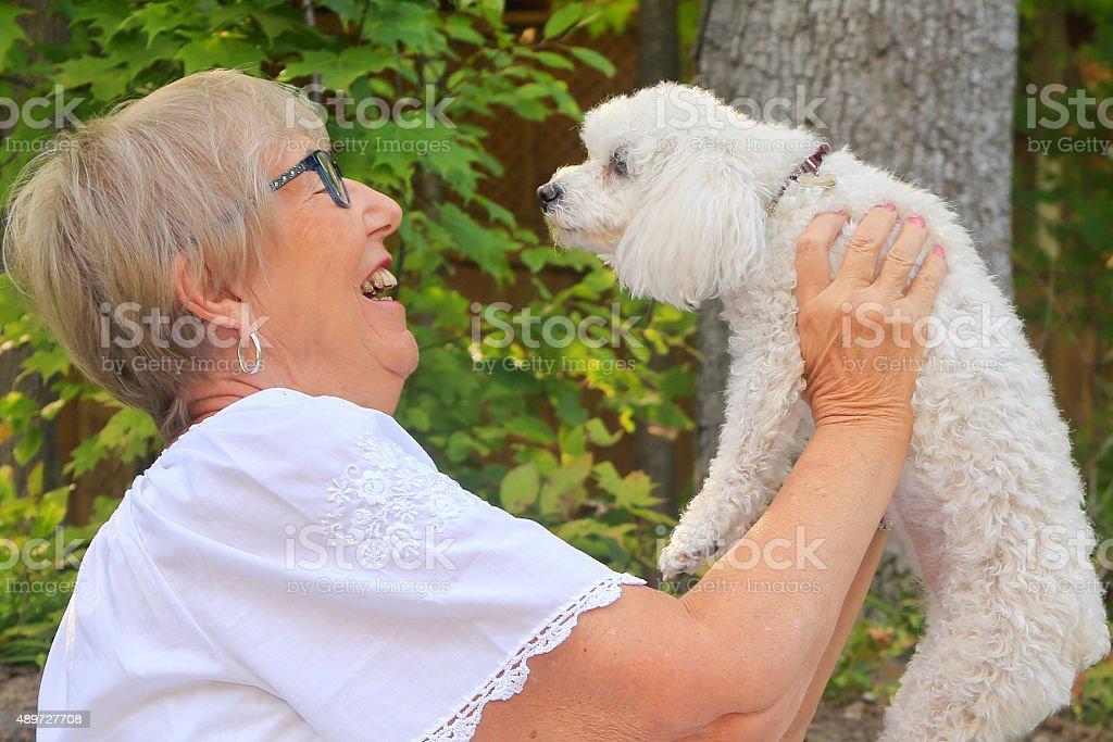 Senior Woman Smiling at her Dog stock photo