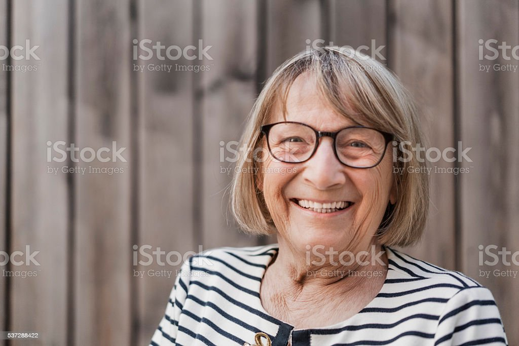 Senior woman smiling in backyard stock photo