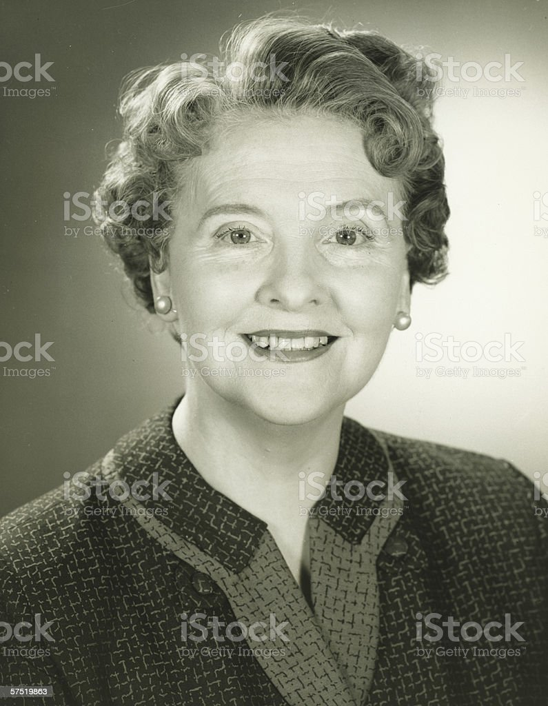 Senior woman smiling in studio, (B&W), close-up, portrait stock photo